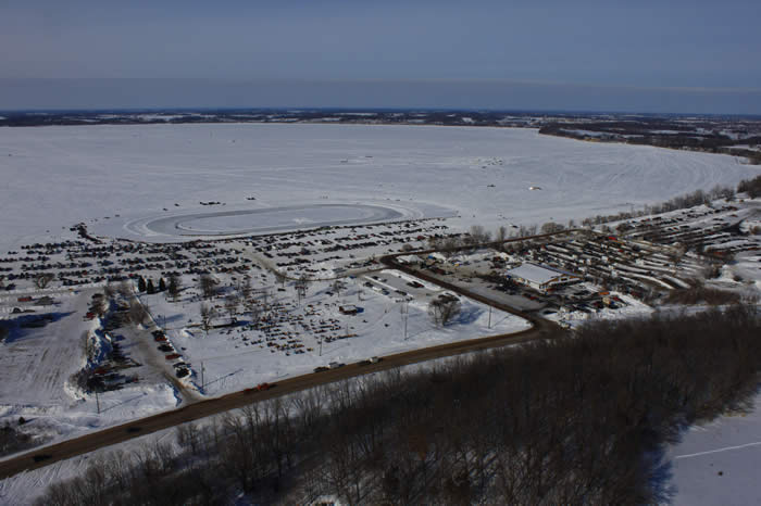 This shows Sunday morning action --- judged show area in the forefront, ballroom to the right and behind it the swap meet area. On the lake are the drag racing lanes to the right, parking to the left and oval track in the background - courtesy of Mike Revier Sky Photos (952-471-7600)
